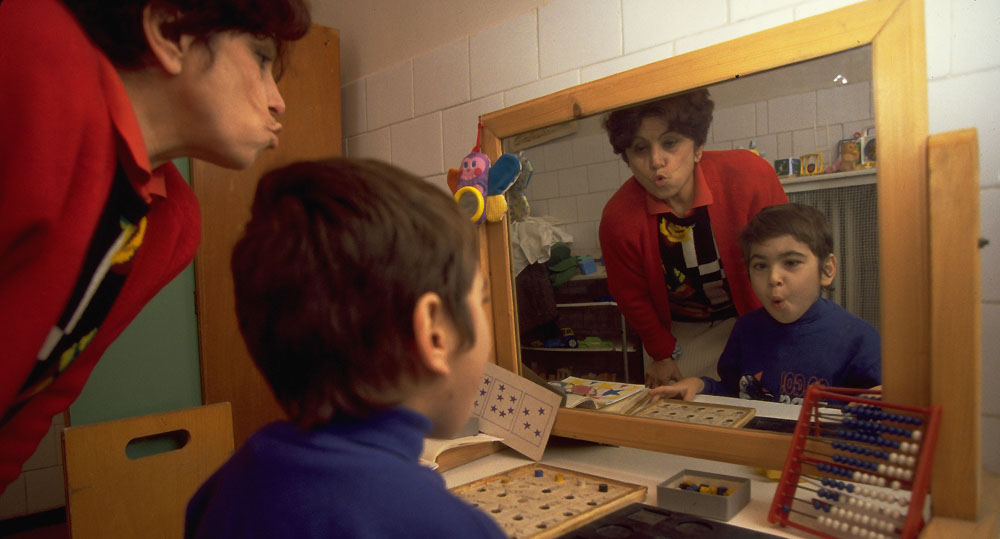 A disabled child practices facial expressions with his tutor in front of a mirror