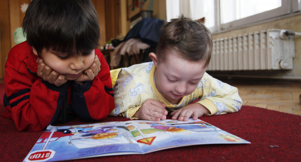 Two children reading a colored book